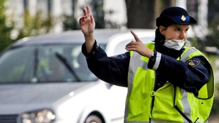 Een agente regelt vrijdag het verkeer rondom Schoorl met een mondkapje op tegen de hevige rookontwikkeling van de brand. ( ANP) Beeld