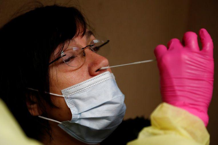Een vrouw wordt in Brussel getest op de aanwezigheid van het coronavirus. Beeld REUTERS
