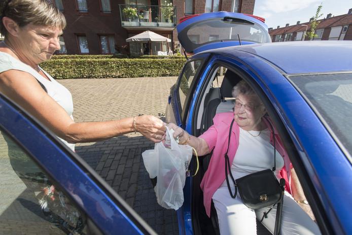 Vrijwilliger Reineke Velema helpt Gerda Oude Breuil (83) met instappen in de auto, waarna ze samen op pad gaan.