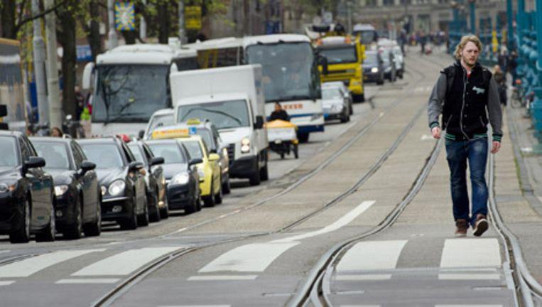 Een man wandelt tijdens de vorige staking over de lege tramrails op het Amsterdamse Damrak. Foto ANP Beeld