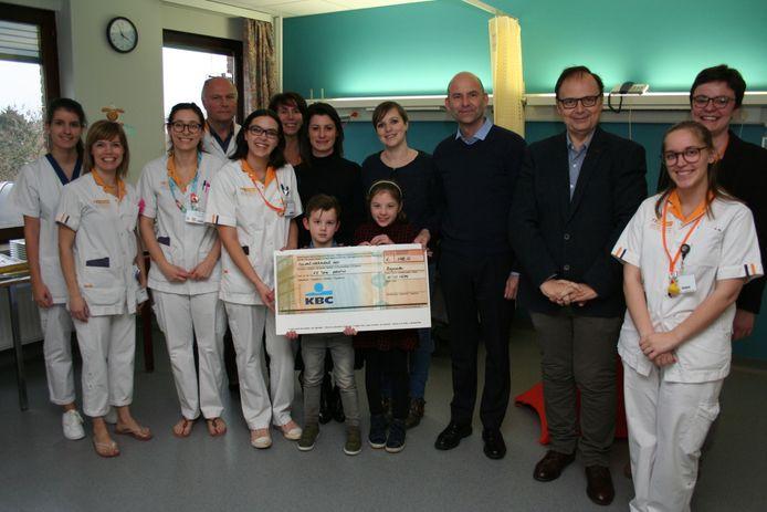 De cheque van de gemeenteschool wordt overhandigd aan de verpleegsters van pediatrie