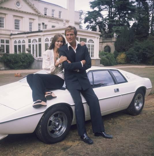 Roger Moore speelde James Bond in The Spy Who Loved Me. Op deze foto leunt hij, samen met Bondgirl Barbara Bach, tegen zijn Lotus Esprit.