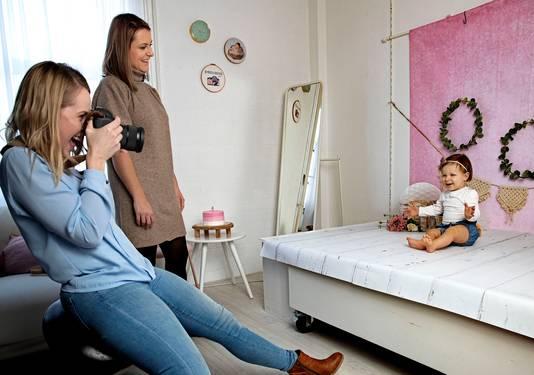 Olivia haar moeder en fotograaf Miranda kijken naar de stralende spruit.