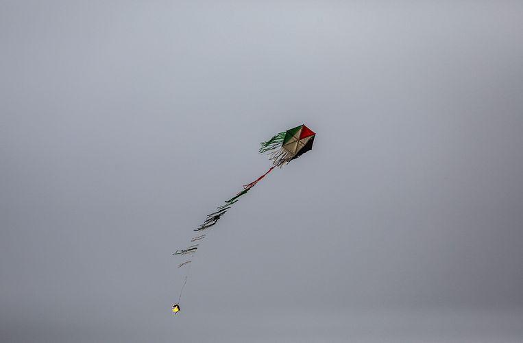 Een vlieger met een molotovcocktail vliegt vlak bij de grens tussen Israël en de Gazastrook.  Beeld EPA