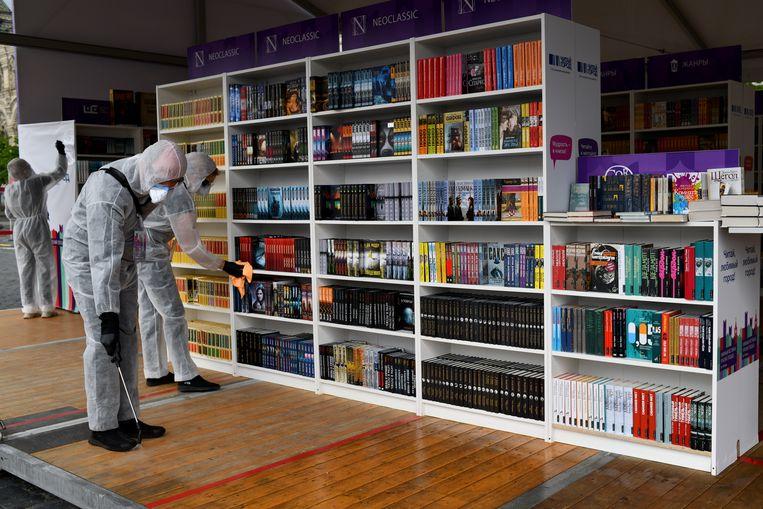 Vrijwilligers ontsmetten boekenstallen en boeken op het Rode Plein. Beeld Yuri Kozyrev / Noor