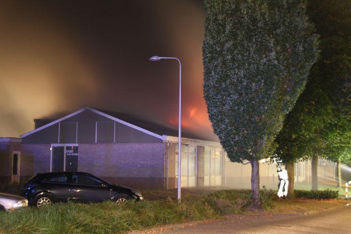 Vlammen slaan uit het dak van de loods.