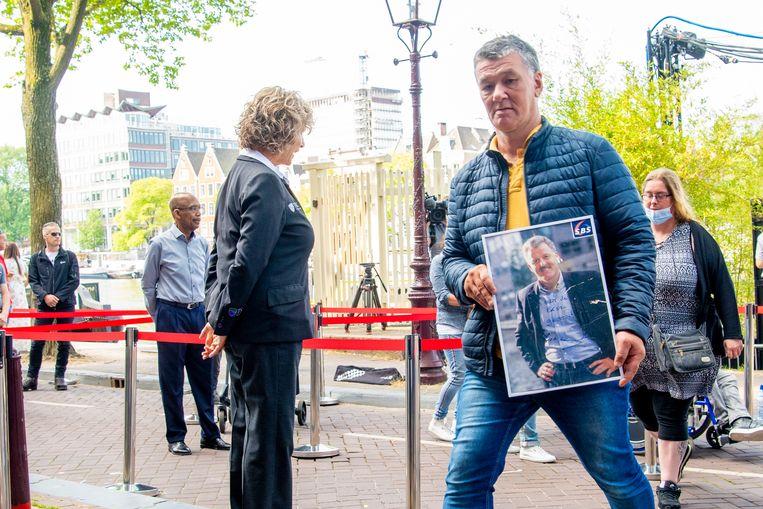 Bij het bewijzen van de laatste eer aan Peter R. de Vries in Amsterdam hadden sommigen een portret van hem bij zich. Beeld Brunopress/Patrick van Emst