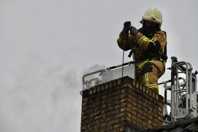 Een van de brandweermannen veegt de schoorsteen vanaf een hoogwerker.