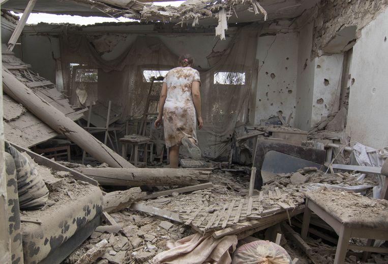 Een Oekraïense vrouw in wat overblijft van haar woning in Marioepol, waar het geweld weer is opgeflakkerd. Beeld AP