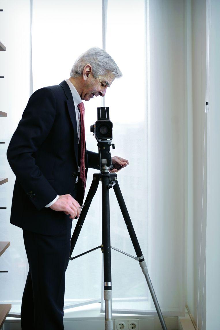 Plasterk fotografeert met zijn Hasselblad bezoekers in zijn werkkamer, 2010. Beeld Joost van den Broek / de Volkskrant