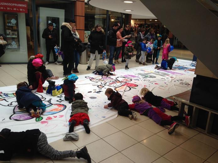 Kinderen werken aan de tekening in de Molenpoortpassage.