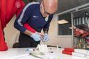 Richard van Beek uit Winterswijk is de fysiektrainer van international Wout Weghorst. Op de foto neemt hij bloed af bij een speler die hij ook traint om te checken hoe het is gesteld met de vitaminen en mineralen.