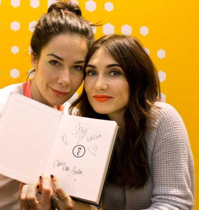 Halina Reijn (L) en Carice van Houten signeren hun boek 'Antiglamour'. Beeld anp