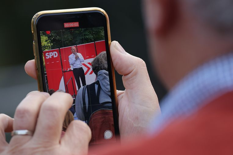 Bezoeker van campagnebijeenkomst neemt het optreden van SPD-lijsttrekker Olaf Scholz op. Beeld Getty Images