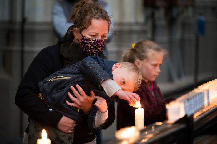 Kerkbezoekers steken een kaarsje aan tijdens meimaand Mariamaand.