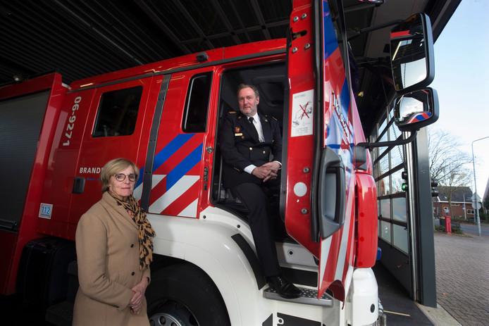 Annette Bronsvoort, burgemeester Oost Gelre, en VNOG-directeur Diemer Kransen bij een bluswagen in de kazeren Lichtenvoorde.