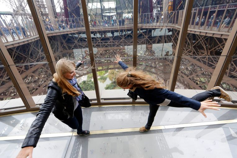 Visitors walk on the new glass floor at the Eiffel Tower in Paris October 6, 2014. The Eiffel Tower inaugurated on Monday a new solid glass floor that  allows visitors to have bird's eye view from 57 metres above the ground. The new attraction is part of the first floor renovation at the Eiffel tower to attract more tourists.  REUTERS/Jacky Naegelen  (FRANCE - Tags: TRAVEL SOCIETY) Beeld Reuters