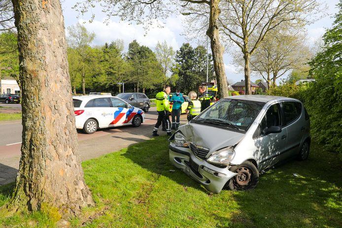 Hulpdiensten op de plaats van het ongeval in Twello, rechts de flink beschadigde auto.