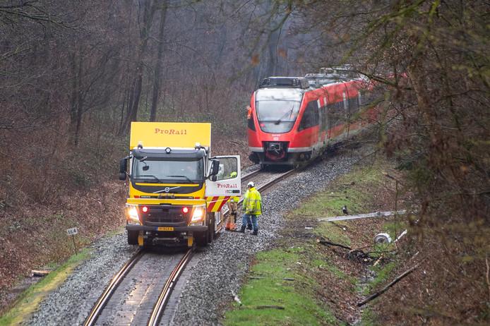 De trein die woensdagavond ontspoorde, nadat hij op een omgevallen boom botste, is weer op de rails gezet. Dat kon niet met een kraan, vanwege de bomen aan beide kanten van het spoor, maar moest met behulp van grote krikken.