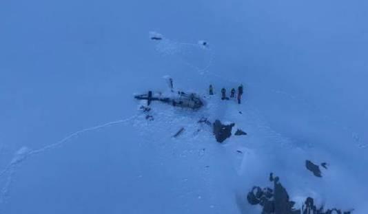 Reddingswerkers bij de wrakstukken van de helikopter die bij de botsing betrokken was.