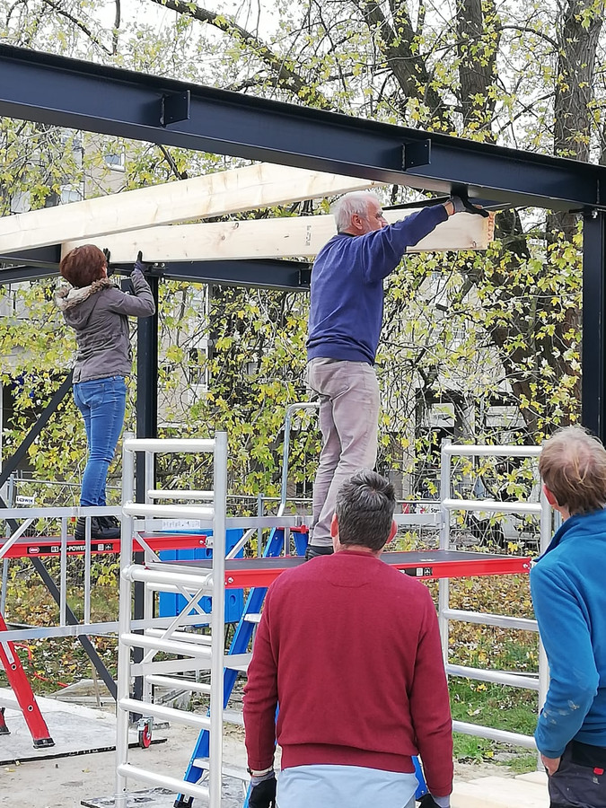 Vrijwilligers helpen mee bij de bouw van het paviljoen bij Doepark De Hagen in Almelo.