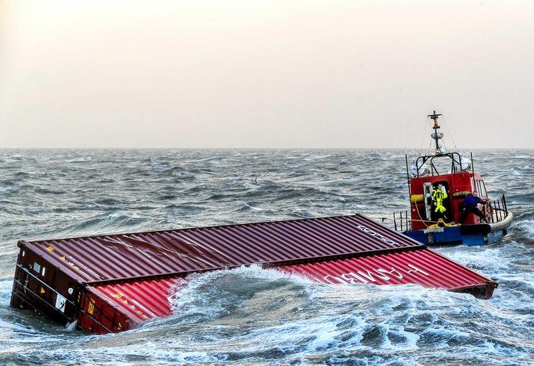Een sleepboot brengt twee overboord geslagen containers van het schip MSC Zoe de haven binnen.  Beeld ANP