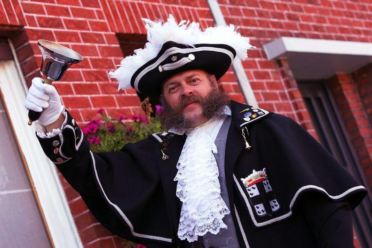 Guy Vandendriessche aan het werk als belleman. Zijn kostuum heeft de kleuren van Izegem: zwart met antracietgrijs.