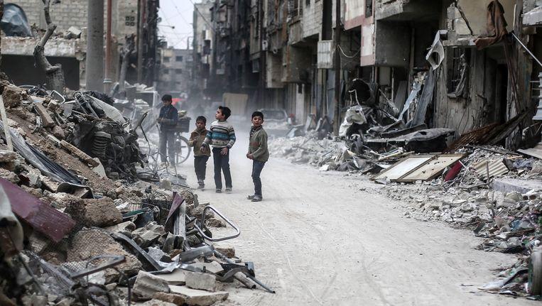 Kinderen te midden van het puin in Douma, Syrië. Het puin is afkomstig van gebouwen die op 25 januari getroffen werden door luchtaanvallen. Beeld EPA