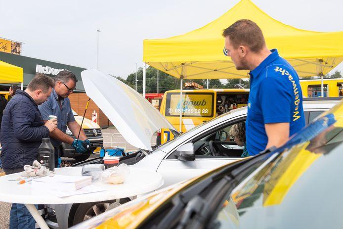 De jaarlijkse vakantiecheck op Hazeldonk. René Nouws (midden) van de Wegenwacht checkt de accu van een auto.