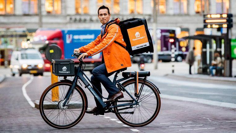 Jitse Groen komt op de fiets aan bij Beursplein 5 voor de beursgang van zijn bedrijf. Beeld anp