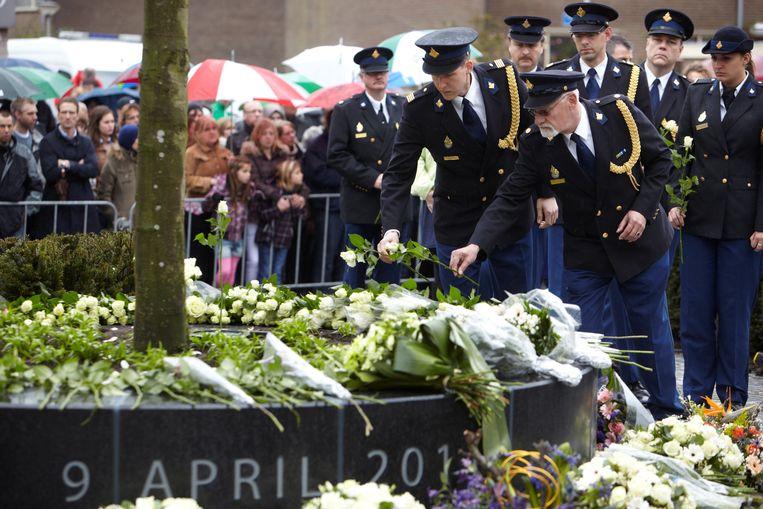Politiemensen leggen bloemen tijdens de eerste herdenking van de schietpartij in Alphen aan den Rijn, op 9 april 2012. Beeld Martijn Beekman