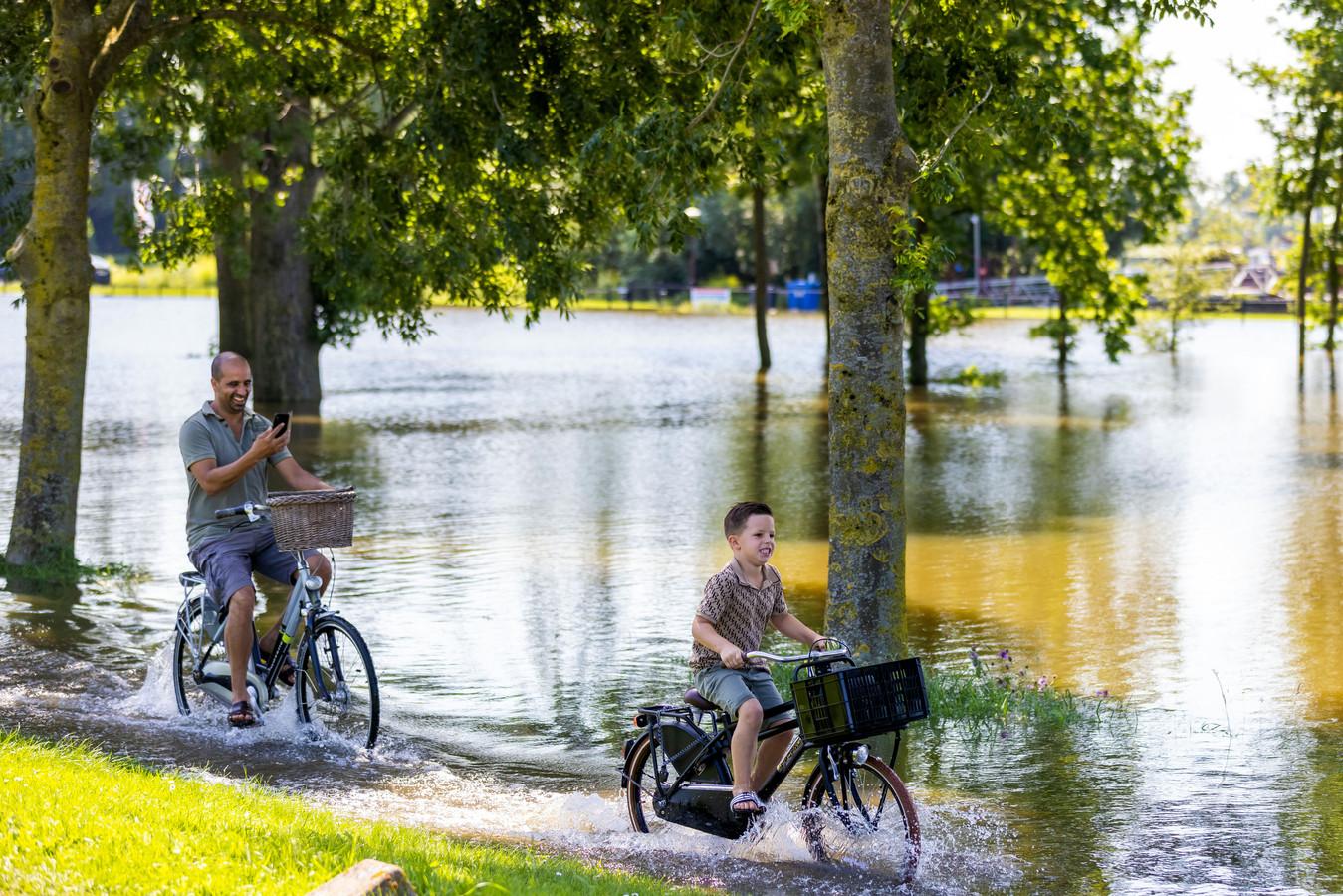 Vader en zoon fietsen door het hoogwater bij De Zandmeren in Kerkdriel.