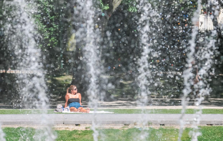 Een vrouw zit in de zon in het Jubelpark in Brussel.