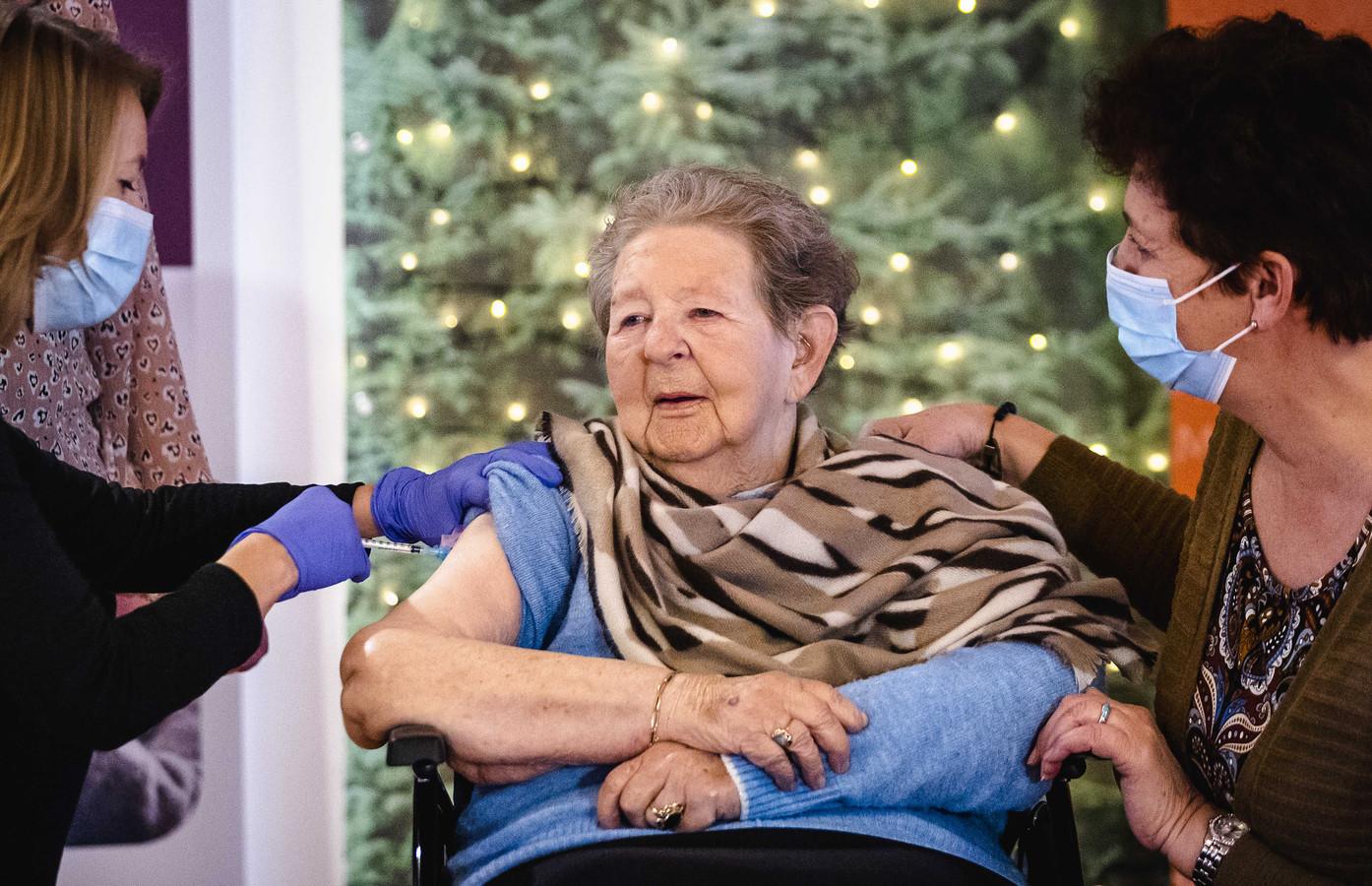 Een oudere vrouw wordt gevaccineerd.