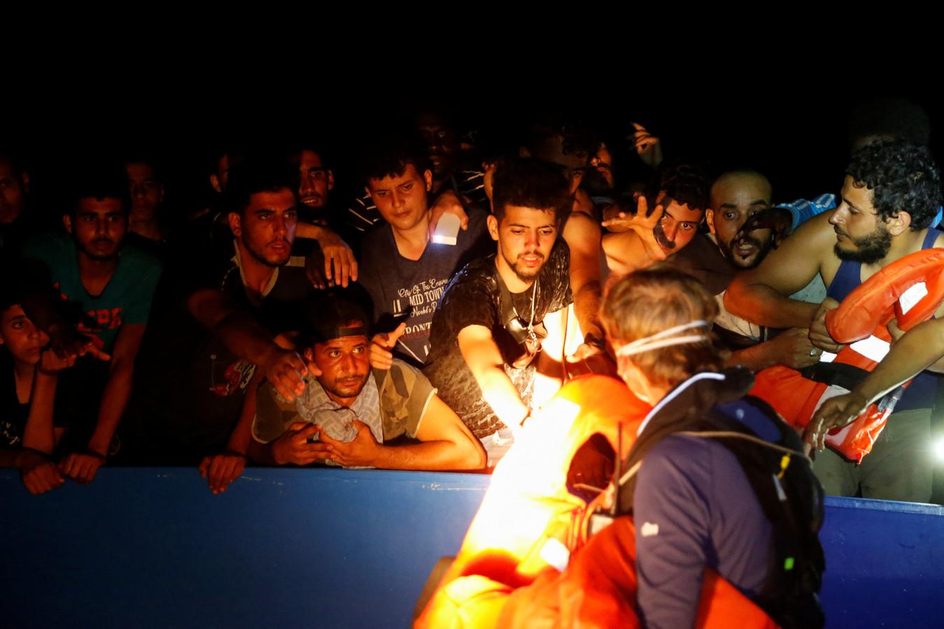 Een bemanningslid van het schip Sea-Watch 3 verdeelt reddingsvesten onder migranten op een overvolle houten boot gedurende een reddingsoperatie voor de kust van Tunesië.