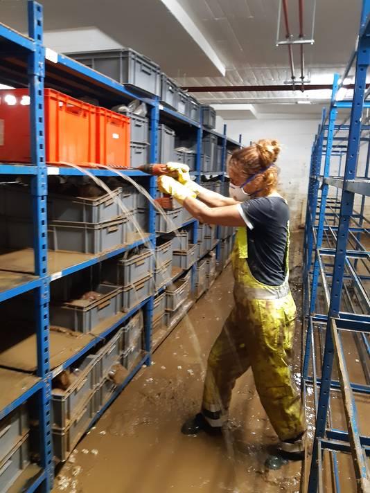 Des trous sont percés dans les caisses pour évacuer l'eau avant de procéder au nettoyage des objets.