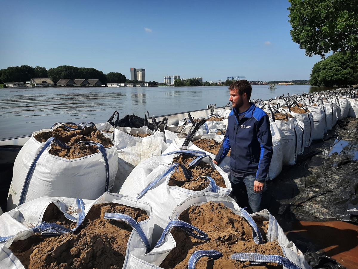 Ivo van Enckevort, inspecteur van Waterschap Limburg, bekijkt de situatie aan de kade in Well. Daar zijn een demontabele kering en big bags met zand geplaatst.