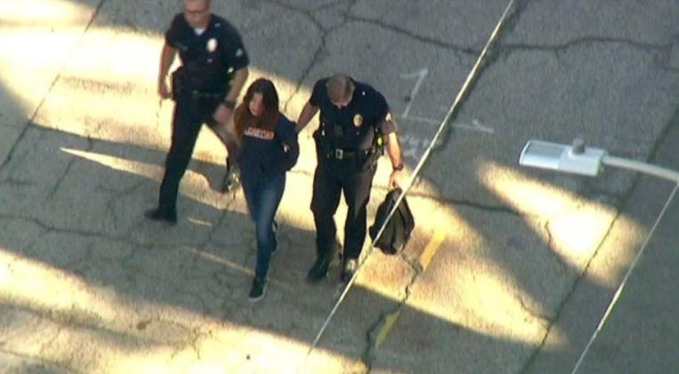 De verdachte wordt door de politie naar buiten geleid.