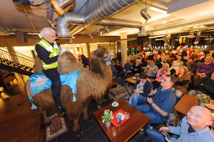 Kunstenaar Pier van Dijk op de Mongoolse kameel, om te pleiten voor 'geld, goederen en diensten' voor de kunstzaal in het Hengelo stationsgebouw.