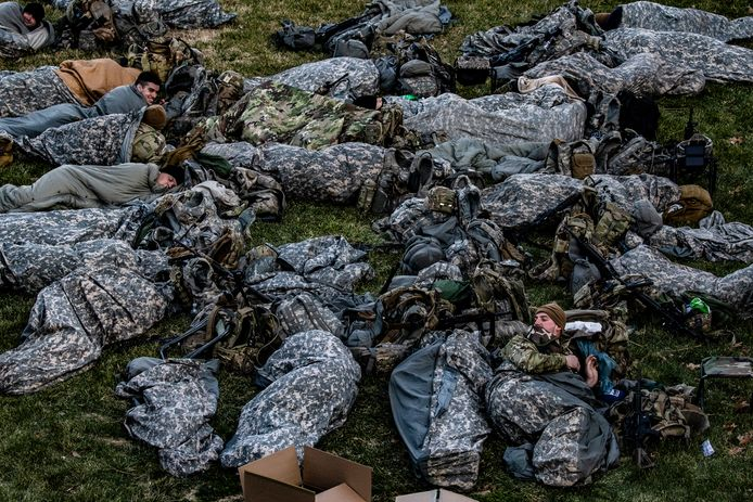 Ongeveer 25.000 leden van de Nationale Garde waren woensdag aanwezig in en rond Washington DC. Een deel van hen rust hier uit op een grasveld nabij het Capitool.