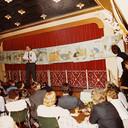 Hans Zoetbrood op de bühne. Achter hem aan de waslijn de illustraties die bij het stapellied horen.