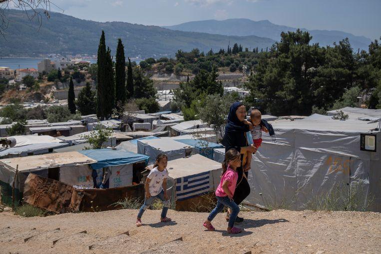 Een Afghaanse vrouw loopt met haar drie kinderen bij een vluchtelingenkamp op het Griekse eiland Samos.  Beeld AP