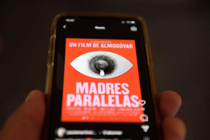 """Une illustration réalisée à Madrid le 10 août 2021 montre un téléphone portable affichant l'affiche du prochain film du réalisateur espagnol Pedro Almodovar, """"Madres Paralelas"""", qui a été conçue par Javier Jaen et temporairement censurée par Instagram pour violation de ses conditions d'utilisation, provoquant une controverse."""