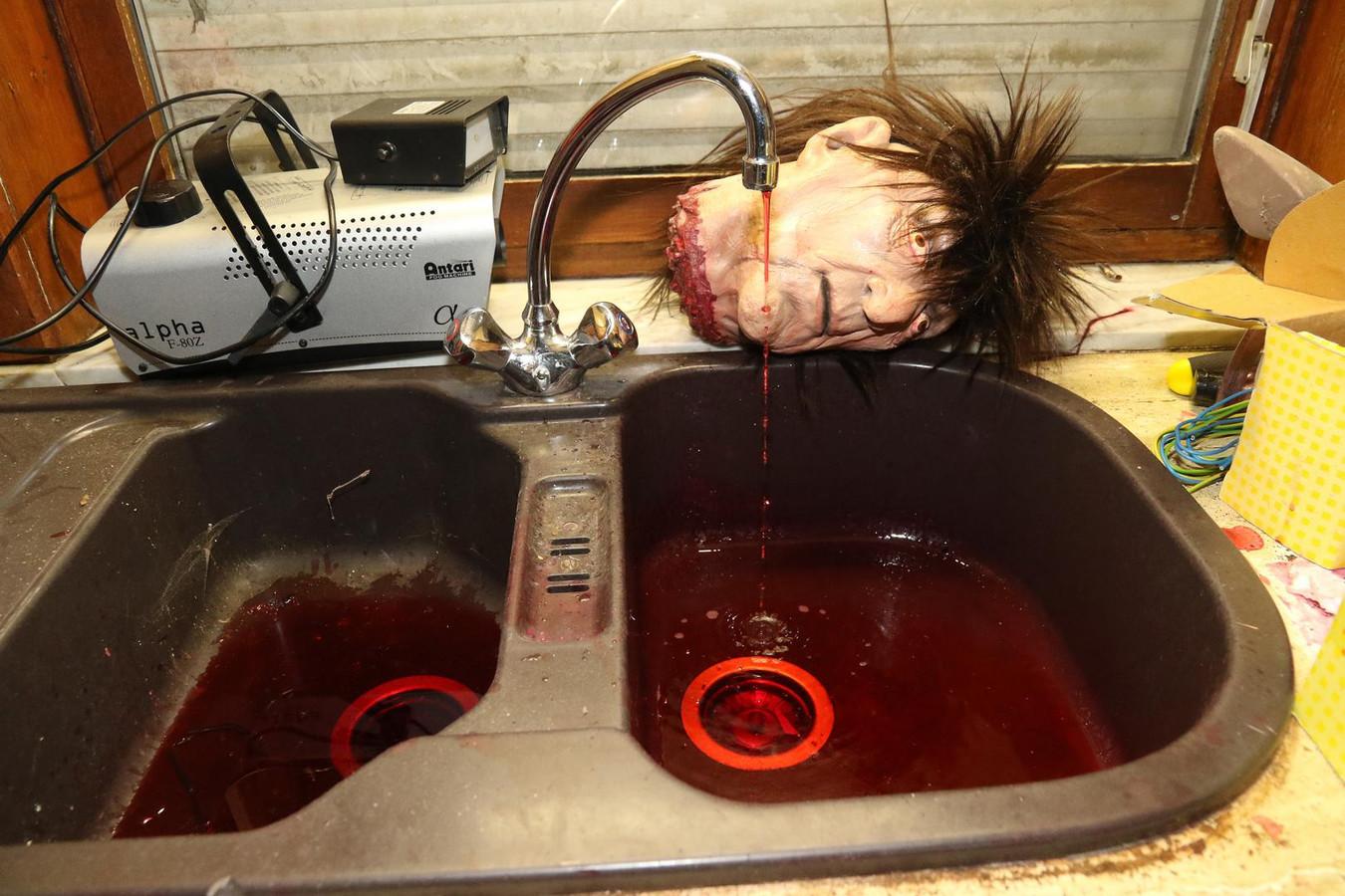 In de keuken ligt een afgehakt hoofd en er loopt bloed uit de kraan.