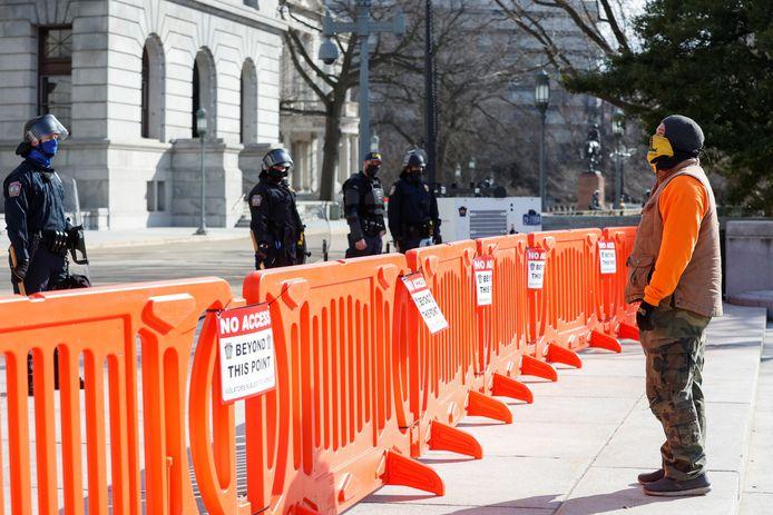 Politieagenten bewaken het State Capitol van Pennsylvania in Harrisburg, rechts een pro-Trumpaanhanger.