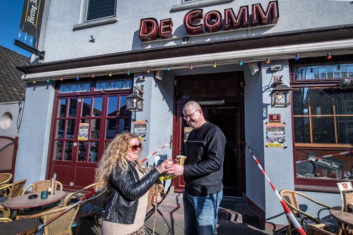 Een medewerker van café-bar De Comm in Groesbeek geeft Eline Zwitserloot een bakje 'tea to go'. De Comm was een van de horecazaken in de regio die bij wijze van protest tegen de coronamaatregelen dinsdag het terras opbouwde. Gasten mochten daar overigens niet zitten.