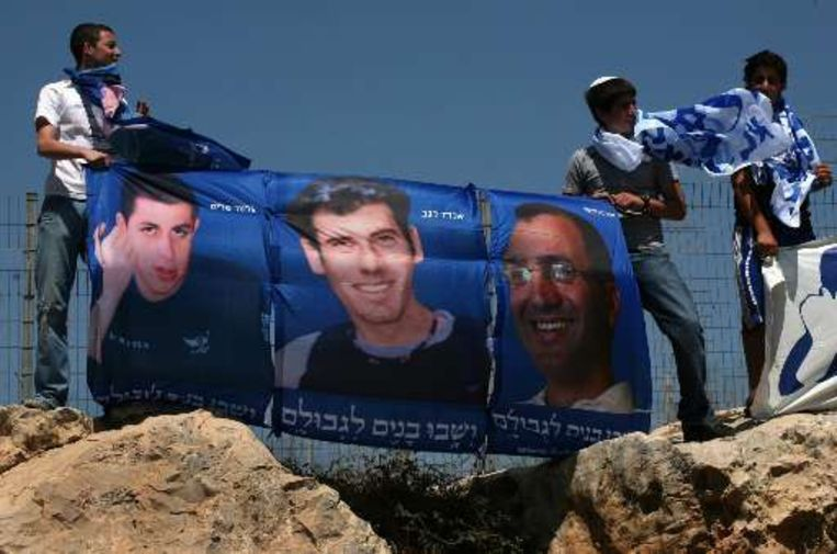 Enkele Israëlische demonstranten houden een vlag vast waar soldaten op staan die worden gevangen gehouden door Hezbollah en Hamas. Beeld UNKNOWN