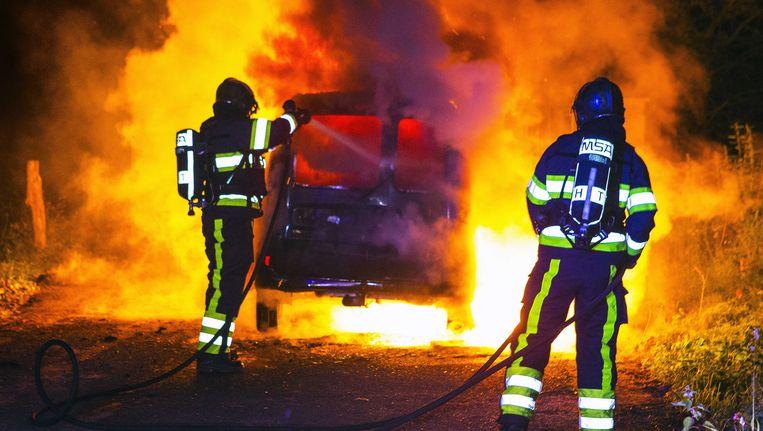 Brandweermannen blussen de brandende auto op de Pettelaar, net buiten de bebouwde kom. Beeld ANP