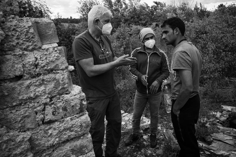Arts Peter Scholten (links) helpt vluchtelingen bij de Bosnisch-Kroatische grens. Een Afghaan (midden) tolkt. Rechts een gewonde vluchteling. Beeld Eddy van Wessel