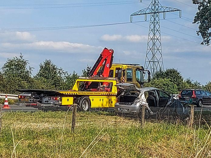 De gehavende auto langs de A73 met de sleepwagen.